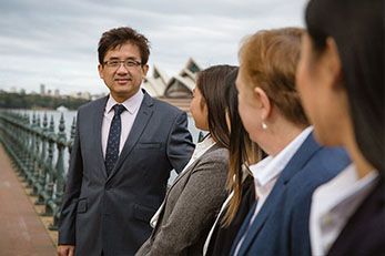 Jeffrey Lawyer in suit looking at his team near Sydney Opera House